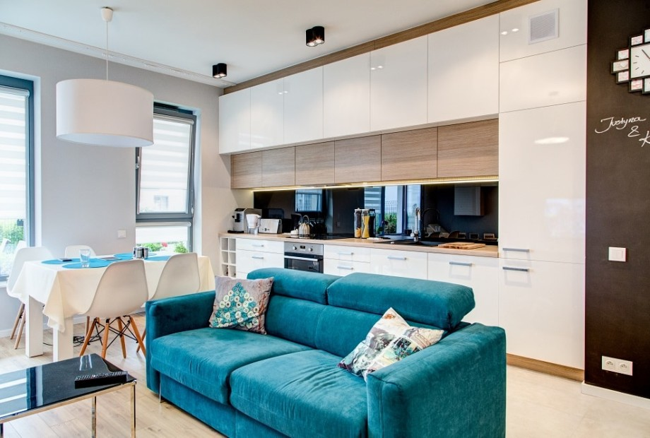 Wykończone wnętrze kuchni i salonu stanowiące jedną przestrzeń podzieloną na strefy