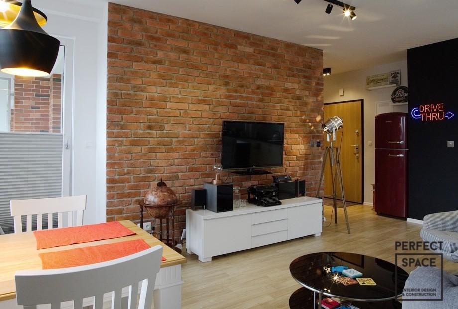Aranzacja-wentrza-salonu-z-wykorzystaniem-cegły-w-naturalnym-kolorze-na-ścianie-za-tv Czerwony jak… Cegła w aranżacji wnętrz. Musisz ją mieć?