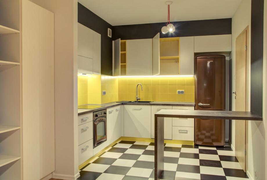 Kuchnia-urzadzona-w-kolorze-bialym-z-drewnianym-blatem-i-zoltymi-frontami-szafek- Niebieskie migdały. Jaki kolor wybrać przy urządzaniu kuchni?
