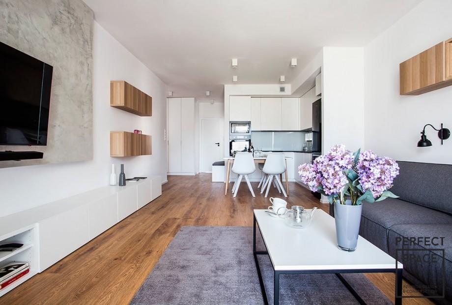 Wnetrze-salonu-z-kuchnia-wykocznone-w-stylu-nowoczesnym-w-bialej-kolorystyce-z-szarymi-elementami Wykańczanie wnętrz: czemu wspólne remonty rujnują związki?